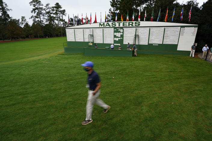 A man wearing a face mask during the coronavirus outbreak walks past the scoreboard during the first round of the Masters golf tournament Friday, Nov. 13, 2020, in Augusta, Ga. (AP Photo/Matt Slocum)