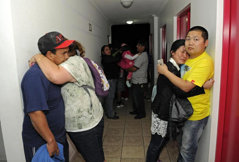 People embrace on the upper floor of an apartment building located a few blocks from the coast where they gathered to avoid a possible tsunami after an earthquake in Iquique, Chile, Tuesday, April 1, 2014. A powerful magnitude-8.2 earthquake struck off Chile's northern coast Tuesday night. There were no immediate reports of injuries or major damage, but buildings shook in nearby Peru and in Bolivia's high altitude capital of La Paz. (AP Photo/Cristian Viveros) NO PUBLICAR EN CHILE