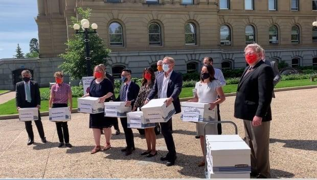 Members of the NDP caucus deliver letters and emails to the premier's office in July 2020 from people opposed to changes to public sector pension plan control and who want Alberta to stay in the Canada Pension Plan.