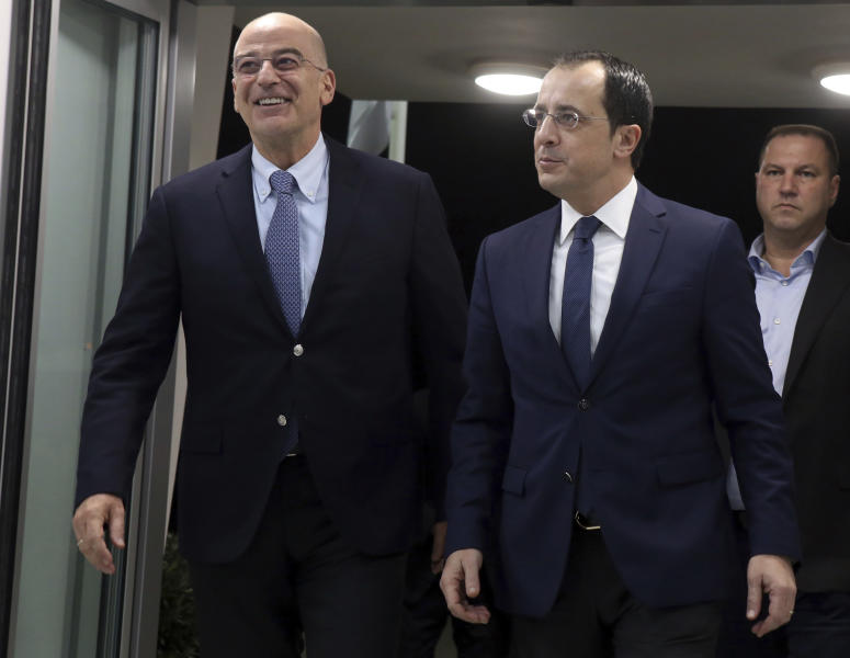 Greece's Foreign Minister Nikos Dendias, left, talks with Cypriot counterpart Nikos Christodoulides before their meeting at Cyprus' main airport in the coastal town of Larnaca on Sunday, December 22, 2019. Dendias stopped off in Cyprus following a visit to Libya for contacts with Libyan National Army leader, General Khalifa Haftar and later in Egypt for a meeting with Foreign Minister Sameh Shoukry. Top of the agenda during Dendias' contacts was a maritime border deal that Turkey signed with Libya's U.N.-recognized government that Greece, Cyprus and Egypt have denounced as contrary to international law.(AP Photo/Philippos Christou)