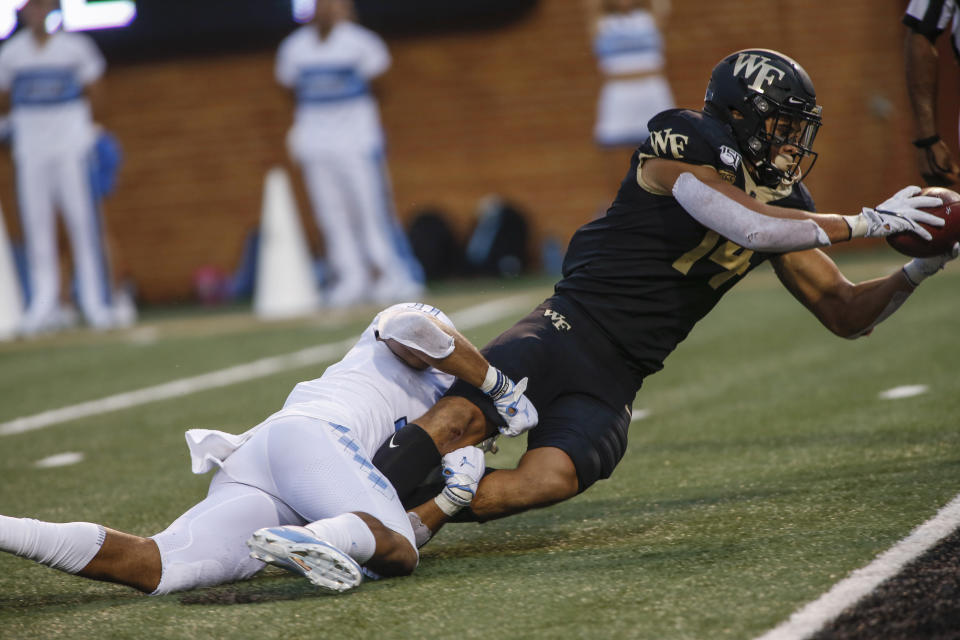 Wake Forest wide receiver Sage Surratt (14) dives for a touchdown after a catch as he is tackled by North Carolina defensive back Myles Wolfolk (11) during the first half of an NCAA college football game in Winston-Salem, N.C., Friday, Sept. 13, 2019. (AP Photo/Nell Redmond)