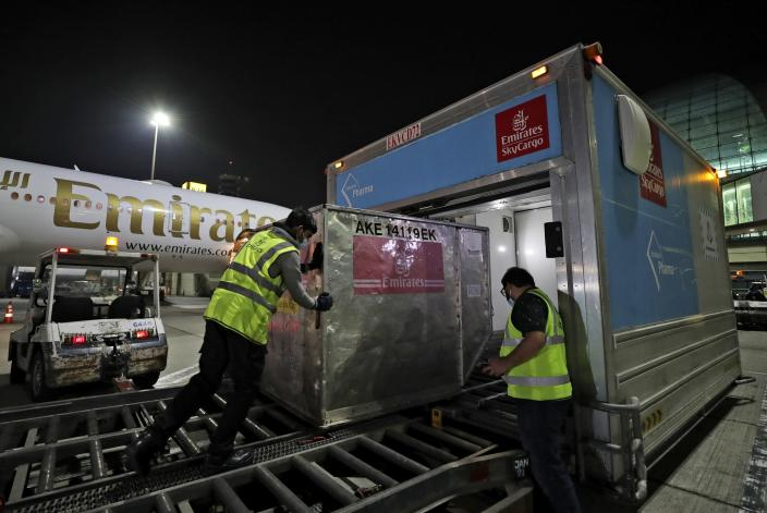 A Pfizer-BioNTech COVID-19 coronavirus vaccine shipment is offloaded from an Emirates Airlines Boing 777 that arrived from Brussels to Dubai International Airport in Dubai, United Arab Emirates, early Sunday, Feb. 21, 2021. As the coronavirus pandemic continues to clobber the aviation industry, Emirates Airlines, the Middle East's biggest airline, is seeking to play a vital role in the global vaccine delivery effort. (AP Photo/Kamran Jebreili)