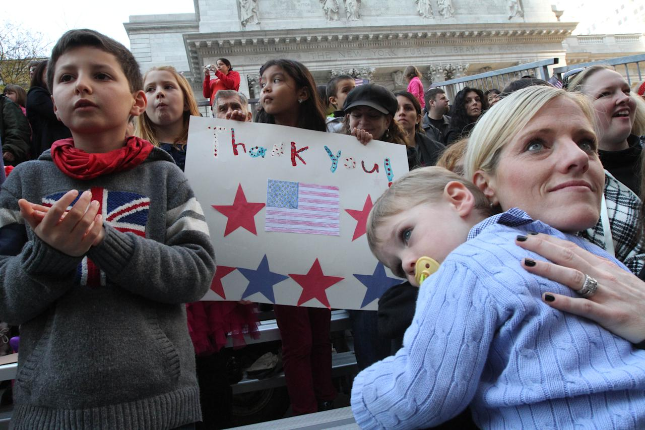 Jamie Trachtenberg, of Chicago, Illinois, right, holds her son Evan Trachtenberg, 2, as they and others watch the Veterans Day Parade makes it's way up New York's Fifth Avenue Sunday Nov. 11, 2012. (AP Photo/Tina Fineberg)