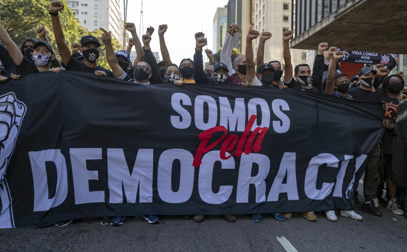"Fans of two distinct soccer clubs hold a banner that reads in Portuguese ""We are for Democracy,"" as they joined forces for an anti-government protest in Sao Paulo, Brazil, Sunday, May 31, 2020. Police used tear gas to disperse anti-government protesters in Brazil's largest city as they began to clash with small groups loyal to President Jair Bolsonaro. (AP Photo/Andre Penner)"