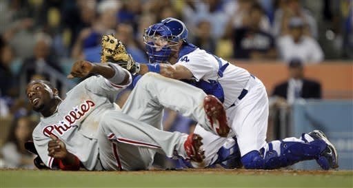 Philadelphia Phillies' Ryan Howard, left, and Los Angeles Dodgers catcher A.J. Ellis peek over to see the umpire call Howard out trying to score during the sixth inning of their baseball game in Los Angeles, Tuesday, July 17, 2012. (AP Photo/Alex Gallardo)