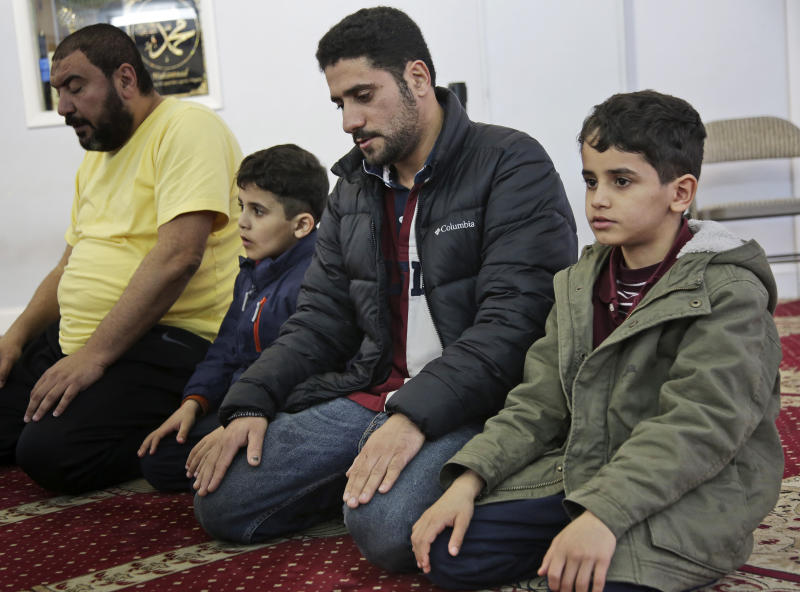In this Thursday, March 21, 2019, photo, Sadek Ahmed, second from right, prays with his sons Adel, 9, right, and Mutaz, 7, second from left, before heading to his evening job in the Brooklyn borough of New York. Their mother, Amena Abdulkarem, is stuck in Yemen with her two younger sons, the boys' brothers. Their family's situation is representative of the toll that the Trump administration's almost-forgotten travel ban has taken on an untold number of families. (AP Photo/Seth Wenig)