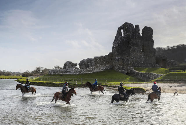 Horses from Christian Williams' stables exercise in the river backdropped by Ogmore Castle in Glamorgan, South Wales, Saturday March 21, 2020. All horse racing fixtures in Great Britain have been suspended because of the coronavirus outbreak. For some people the COVID-19 coronavirus causes mild or moderate symptoms, but for others it causes severe illness. (David Davies / PA via AP)