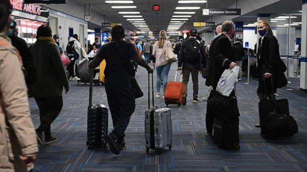 PHOTO: Passengers walk through a crowded terminal at Dulles International airport in Dulles, Va., Dec. 27, 2020. (Andrew Caballero-Reynolds/AFP via Getty Images)