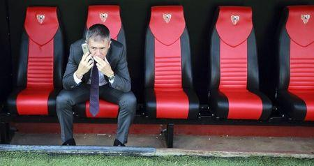 Levante's coach Lucas Alcaraz sits on the bench as he speaks on the mobile phone at the end of their soccer match against Sevilla in Seville