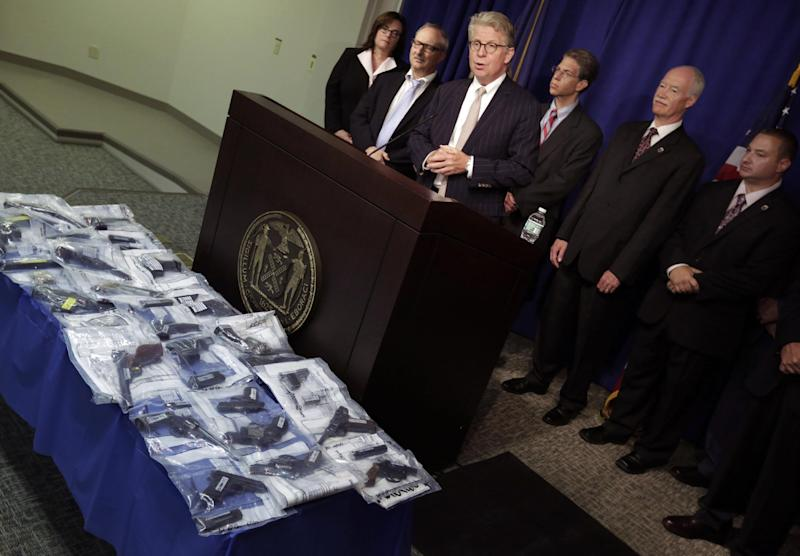 Manhattan District Attorney Cyrus R. Vance Jr., center, addresses news conference as seized guns are displayed, in New York, Tuesday, July 9, 2013. Nine people, members of the infamous Bonanno crime family, have been indicted on enterprise corruption charges. (AP PhotoRichard Drew)