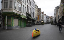 A man rides a pedal car down what would normally be a busy tourist area in the historic center of Antwerp, Belgium, Saturday, March 14, 2020. Belgium has closed schools, restaurants and bars, as as well as cancelled sporting and cultural events in an effort to contain the spread of the coronavirus. For most people, the new coronavirus causes only mild or moderate symptoms, such as fever and cough. For some, especially older adults and people with existing health problems, it can cause more severe illness, including pneumonia. (AP Photo/Virginia Mayo)