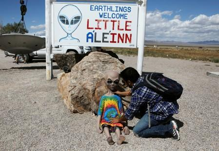 An attendee poses an alien doll at the Little A'Le'Inn as an influx of tourists responding to a call to 'storm' Area 51, a secretive U.S. military base believed by UFO enthusiasts to hold government secrets about extra-terrestrials, is expected