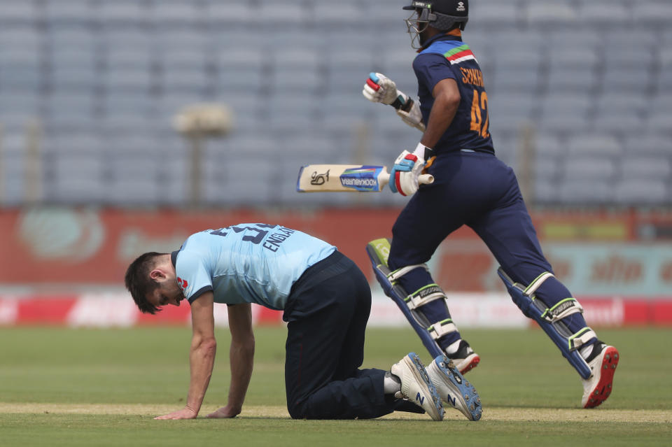 England's Mark Wood, left, reacts after bowling a delivery as India's Shikhar Dhawan runs past during the first One Day International cricket match between India and England at Maharashtra Cricket Association Stadium in Pune, India, Tuesday, March 23, 2021. (AP Photo/Rafiq Maqbool)