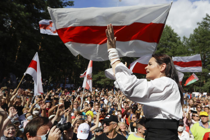 FILE In this file photo taken on Sunday, Aug. 2, 2020, Sviatlana Tsikhanouskaya, candidate for the presidential elections greets people waving old Belarus flags during a meeting to show her support , in Brest, 326 km (203,7 miles) southwest of Minsk, Belarus. Belarus' authoritarian President Alexander Lukashenko faces a perfect storm as he seeks a sixth term in the election held Sunday, Aug. 9, 2020 after 26 years in office. Mounting public discontent over the worsening economy and his government's bungled handling of the coronavirus pandemic has fueled the largest opposition rallies since the Soviet collapse. (AP Photo/Sergei Grits)