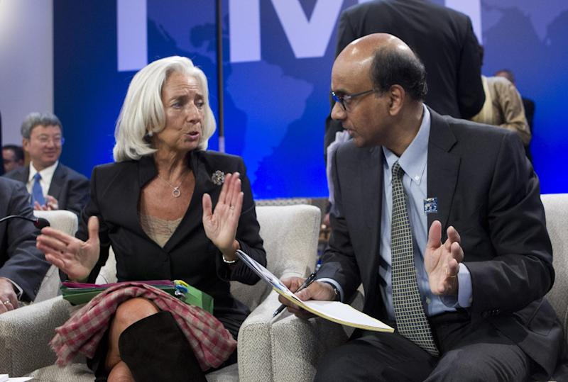 International Monetary Fund (IMF) Managing Director Christine Lagarde, speaks with Singaporean Minister for Finance Tharman Shanmugaratnam, who is also the chairman of the IMFC, before a meeting of the IMFC, during the World Bank/IMF Annual Meetings at IMF headquarters, Saturday, Oct. 12, 2013, in Washington. World finance officials prepared to wrap up three days of meetings in Washington, where fretting about the risk of an unprecedented U.S. debt default overshadowed myriad worries about a shaky global economic recovery. ( AP Photo/Jose Luis Magana)