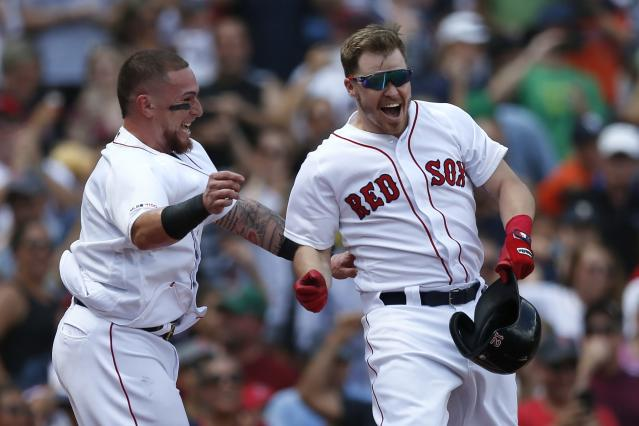 Boston Red Sox's Brock Holt, right, celebrates his game-winning RBI single with Christian Vazquez during the 10th inning of a baseball game against the Kansas City Royals that was suspended by rain with the scored tied on Aug. 8, and continued at Fenway Park in Boston, Thursday, Aug. 22, 2019. (AP Photo/Michael Dwyer)