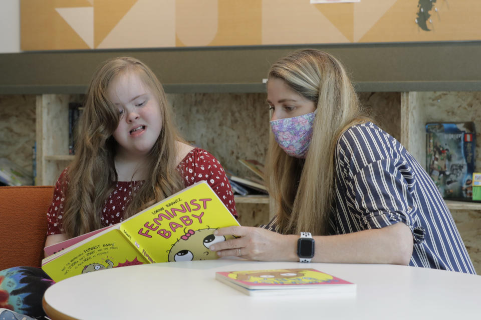 Tricia Nora, right, a pediatric nurse practitioner who works at Mary's Place, a family homeless shelter located inside an Amazon corporate building, reads a book to Emilyanne Wade, 12, who lives at the shelter, Wednesday, June 17, 2020, in Seattle. The facility is home to the Popsicle Place shelter program, an initiative to address the needs of homeless children with life-threatening health conditions. (AP Photo/Ted S. Warren)
