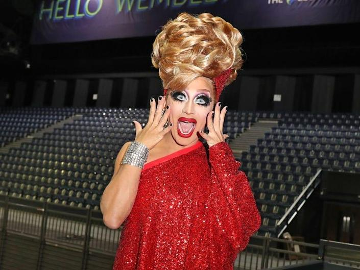 Bianca Del Rio dressed in red dress and pretending to scream