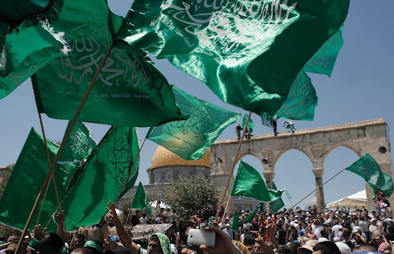 Hamas supporters wave the faction's flag during a demonstration outside the Dome of the Rock mosque in Jerusalem's old city on July 10, 2015