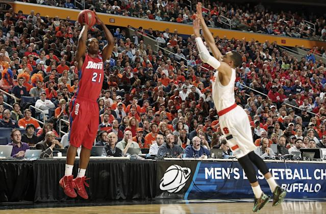 Dayton's Dyshawn Pierre (21) shoots over Syracuse's Tyler Ennis (11) during the first half of a third-round game in the NCAA men's college basketball tournament in Buffalo, N.Y., Saturday, March 22, 2014. (AP Photo/Bill Wippert)