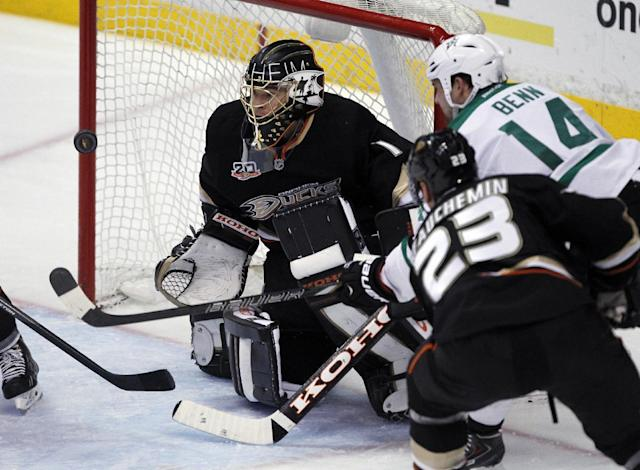 Anaheim Ducks goalie Jonas Hiller, left, of Switzerland makes the stop on a shot by Dallas Stars left wing Jamie Benn (14) with Ducks defenseman Francois Beauchemin (23) trailing the play in the second period of an NHL hockey game Saturday, Feb. 1, 2014, in Anaheim, Calif. (AP Photo/Alex Gallardo)