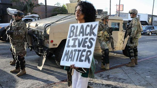PHOTO: A woman carries a 'Black Lives Matter' sign past U.S. National Guard troops, May 31, 2020, in Los Angeles. (Mario Tama/Getty Images)