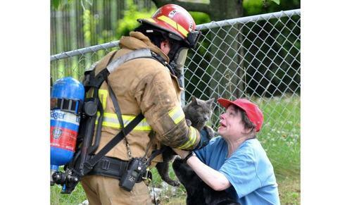 Firefighter handing cat to tearful woman