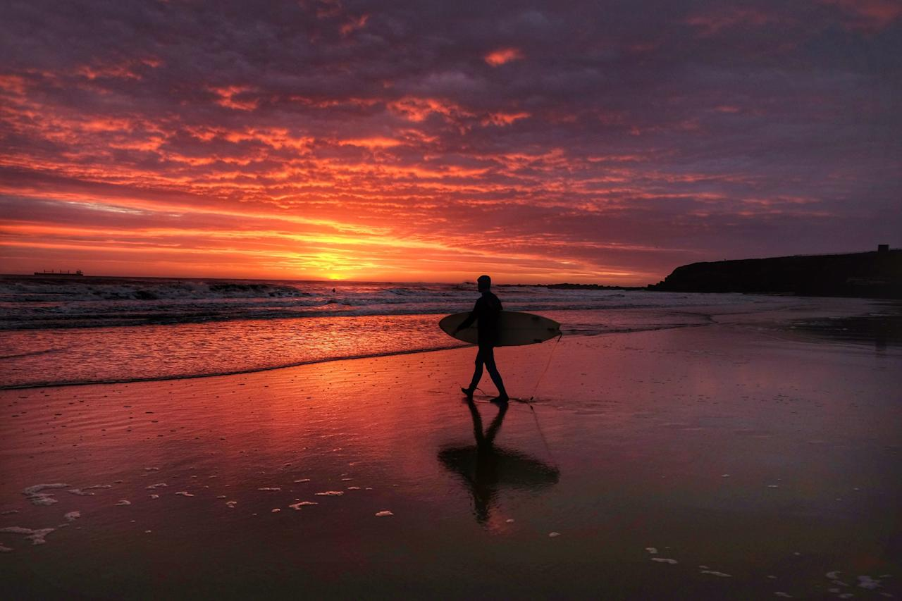 <p>A surfer enters the water during sunrise at Tynemouth beach in North Tyneside. (PA) </p>