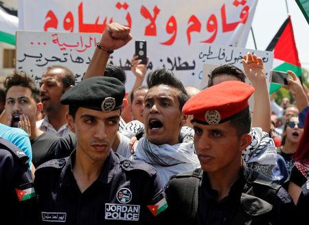 """FILE PHOTO: Protestors chant slogans during a demonstration near the Israeli embassy in Amman, Jordan July 28, 2017. The banner reads, """"Resist don't submit"""". REUTERS/Muhammad Hamed/File Photo"""