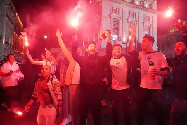 Fans let off flares as they celebrate in Piccadilly Circus, central London, on Wednesday