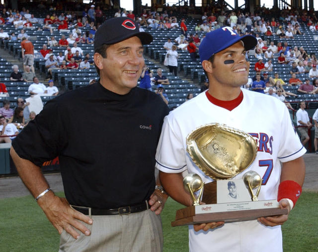 FILE - In this June 10, 2002, file photo, Cincinnati Reds Hall of Fame catcher Johhny Bench, left, and Texas Rangers catcher Ivan Rodriguez watch a short movie on the stadium scoreboard before the start of the Reds' game against the Rangers in Arlington, Texas. Rodriguez holds his 10th consecutive Golden Glove trophy presented to him by Bench. The stadium halfway between Dallas and Fort Worth, first known as The Ballpark in Arlington, is down to its final homestand after more than 2,000 regular season games over 26 seasons. (AP Photo/Tim Sharp, File)