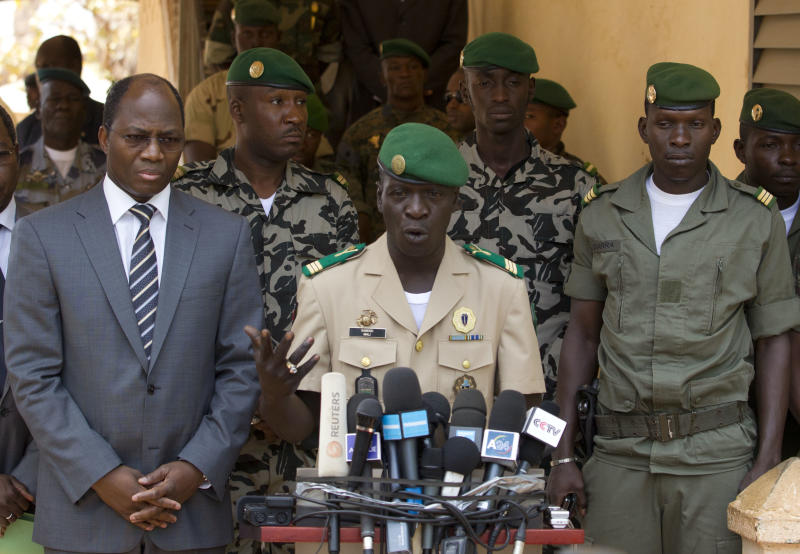 Coup leader Capt. Amadou Haya Sanogo, center, is accompanied by Burkina Faso Foreign Affairs Minister Djibril Bassole, left, as he addresses the media at junta headquarters in Kati, outside Bamako, Mali, on Sunday, April 1, 2012. The leader of Mali's recent coup says he is reinstating the nation's previous constitution amid international pressure to restore constitutional order. Sanogo said a national convention would be held to organize elections, but he did not announce a timeline for the elections. (AP Photo/Rebecca Blackwell)