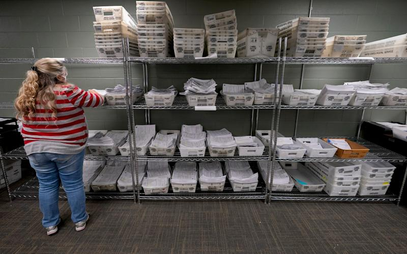 Election worker Nancy Wilcox looks through mail-in ballot requests - Charlie Riedel/AP