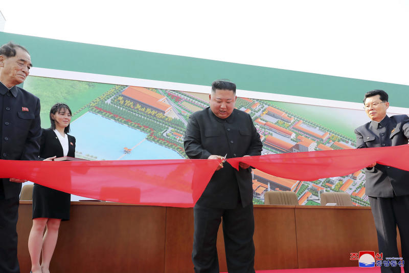 This photo shows North Korean leader Kim Jong Un, center, apparently cutting a tape during his visit to a fertiliser factory.