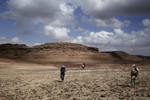 In this March 30, 2019 photo, Umm Yasser, center, leads women on a trek in the mountains, near Wadi Sahw, Abu Zenima, in South Sinai, Egypt. Umm Yasser is breaking new ground among the deeply conservative Bedouin of Egypt's Sinai Peninsula. Women among the Bedouin almost never work outside the home, and even more rarely do they interact with outsiders. But Umm Yasser is one of four women from the community who for the first time are working as tour guides. (AP Photo/Nariman El-Mofty)