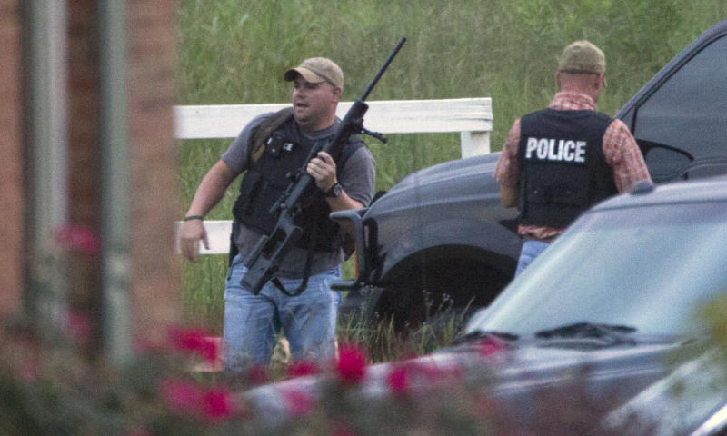 Police officers with automatic weapons stand outside a home in Montgomery, Ala., Monday, June 11, 2012. Officials say it is where they believe a suspect in the shooting deaths of three people in Auburn is hiding. Officers have detected someone moving around, but haven't made contact with whoever's in there.  (AP Photo/Dave Martin)