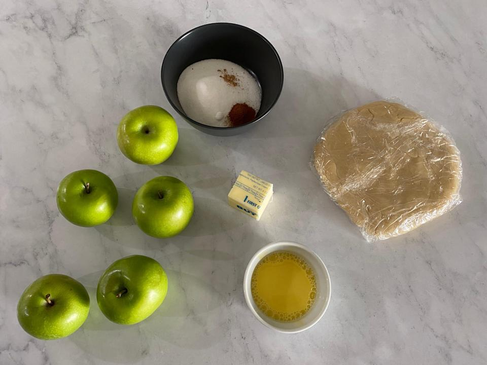 Flat lay of green apples, sugar, butter, dough, and egg yolks.