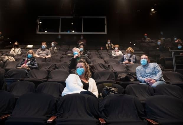 People wear face masks as they wait for the start of a performance Centaur Theatre in Montreal, where a limited audience is now allowed.