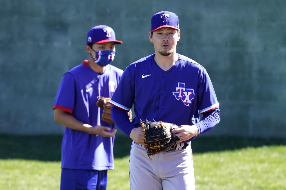 Texas Rangers pitcher Kohei Arihara, from Japan, walks to a drill during spring training baseball practice Wednesday, Feb. 24, 2021, in Surprise, Ariz. (AP Photo/Charlie Riedel)