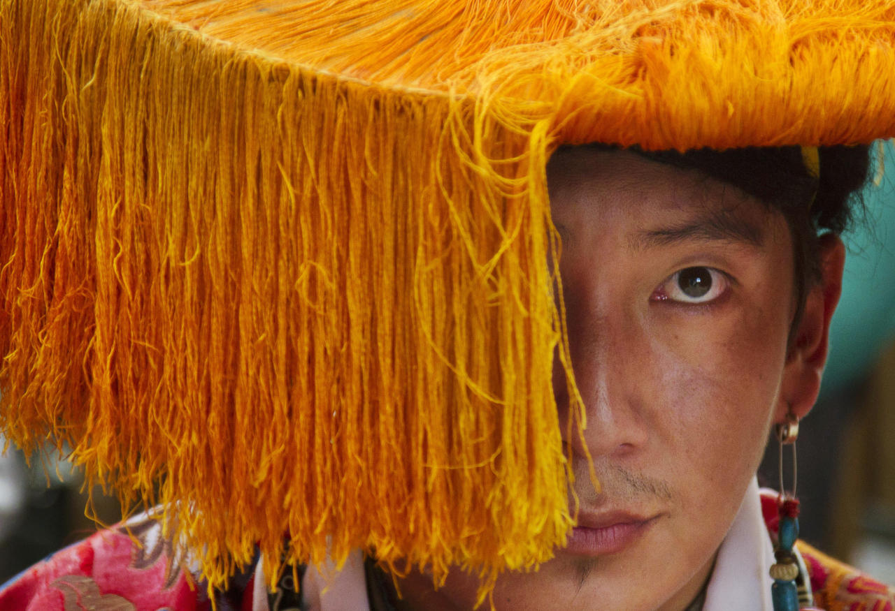 An exile Tibetan in traditional costume waits to perform a dance at Tsuglakhang temple in Dharmsala, India, Friday, July 6, 2012. The Dalai Lama celebrates his 77th birthday with festivities held for the entire day at the temple complex. (AP Photo/Ashwini Bhatia)