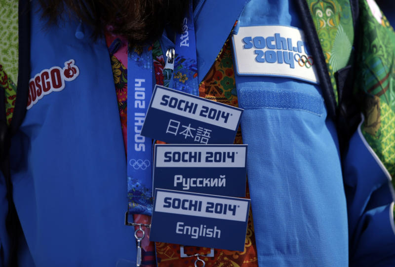 FILE - In this Feb. 6, 2014 file photo, a volunteer wears badges indicating the languages she speaks, during the men's snowboard slopestyle qualifying at the Rosa Khutor Extreme Park in Krasnaya Polyana, Russia, ahead of the 2014 Winter Olympics. More than 20 years after emerging from seven decades of Communism, many Russians, who long endured shabby Soviet construction and slow-moving workers, are encouraged by the progress they see in Sochi. The volunteer corps at the Olympics and staff at hotels have proved to be not just competent but friendly. (AP Photo/Andy Wong, File)
