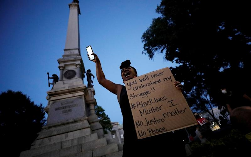 A protester speaks to the crowd underneath the Confederate monument last month during nationwide unrest following the death of George Floyd - Reuters