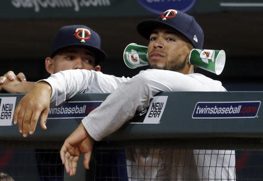 Minnesota Twins pitcher Fernando Romero watches from the dugout with drink cups attached to his ears during the team's baseball game against the Detroit Tigers on Tuesday, May 22, 2018, in Minneapolis. The Twins won 6-0. (AP Photo/Jim Mone)