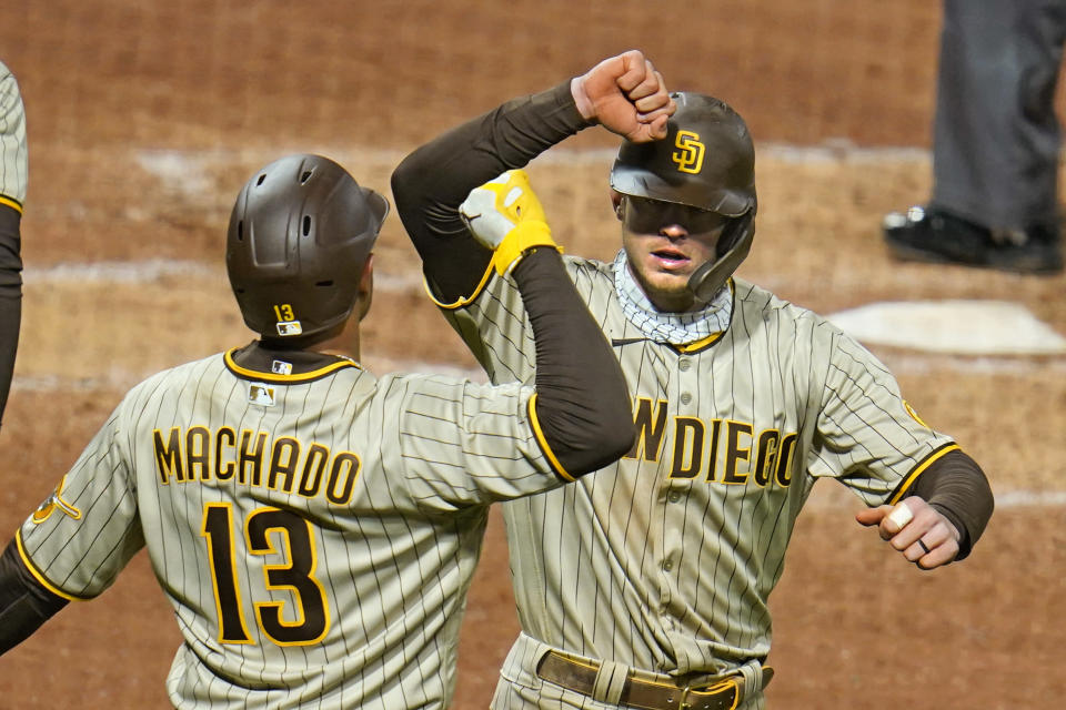 San Diego Padres' Wil Myers, right, celebrates with Manny Machado as they head back to the dugout after scoring on Myers' two-run home run off Pittsburgh Pirates starting pitcher Luis Oviedo during the sixth inning of a baseball game in Pittsburgh, Monday, April 12, 2021. (AP Photo/Gene J. Puskar)