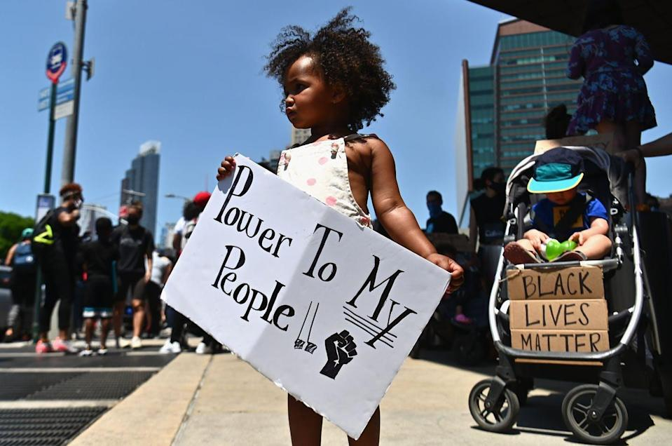 A little Black girl on a street holds a sign that reads 'Power to my people!!'
