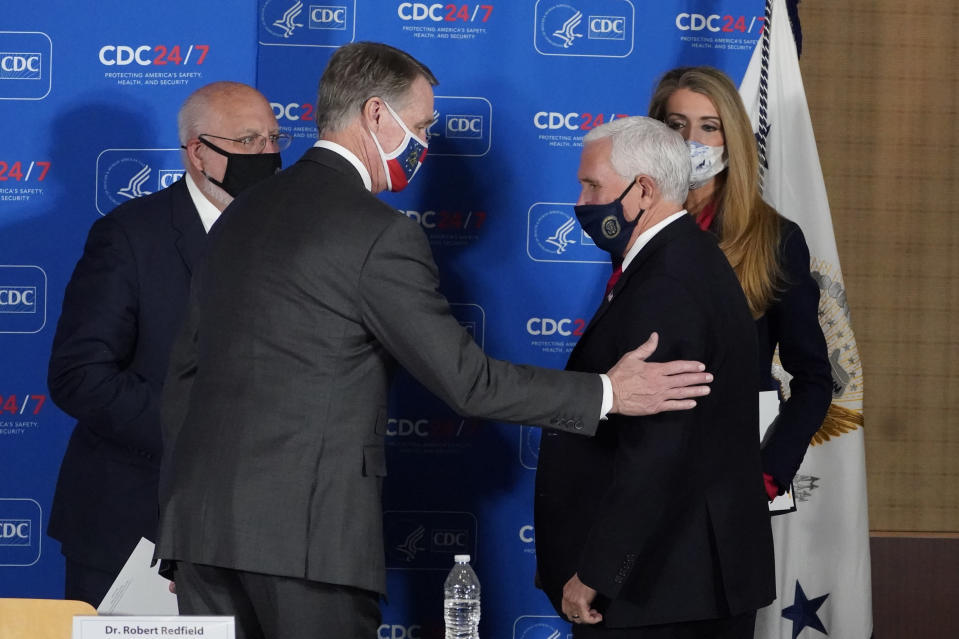 Vice President Mike Pence, right, speaks with Sen. David Perdue, R-Ga., and Sen. Kelly Loeffler, R-Ga, as Centers for Disease Control and Prevention director Dr. Robert Redfield looks on after a meeting on COVID-19 at the CDC Friday, Dec. 4, 2020, in Atlanta. (AP Photo/John Bazemore)