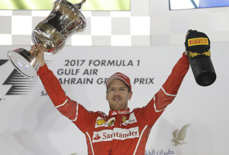 Ferrari driver Sebastian Vettel of Germany, right, celebrates after winning the Bahrain Formula One Grand Prix at the Formula One Bahrain International Circuit in Sakhir, Bahrain, Sunday, April 16, 2017. (AP Photo/Luca Bruno)