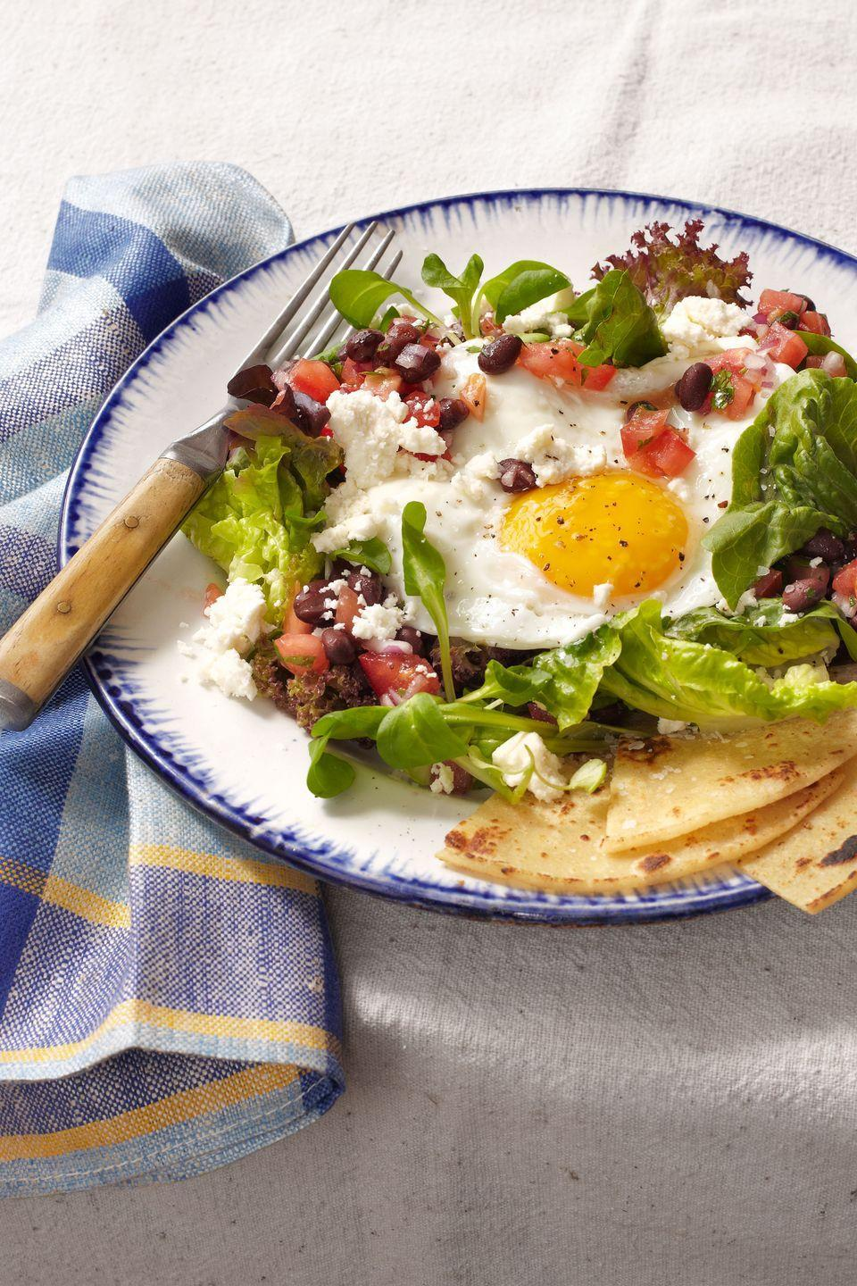 """<p>A bright, sunny-side-up fried egg steals the show on this Southwestern salad topped with queso fresco, cilantro, and a citrusy black-bean-and-tomato salsa.</p><p><strong><a href=""""https://www.countryliving.com/food-drinks/recipes/a6175/huevos-rancheros-salad-recipe-clv0214/"""" rel=""""nofollow noopener"""" target=""""_blank"""" data-ylk=""""slk:Get the recipe"""" class=""""link rapid-noclick-resp"""">Get the recipe</a>.</strong></p>"""