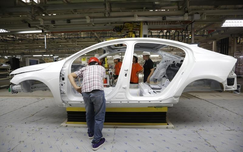 Workers prepare to assemble parts of a Volvo car at an assembly line of the new Volvo automobile manufacturing plant in Chengdu