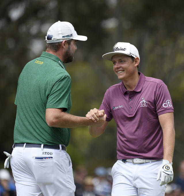 Australia's Marc Leishman, left, and Cameron Smith shake hands during the World Cup of Golf in Melbourne, Australia, Sunday, Nov. 25, 2018. (AP Photo/Andy Brownbill)
